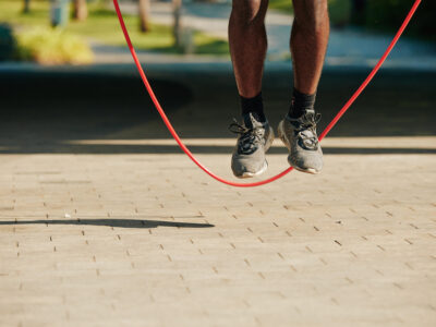 Feet of sportsman jumping with skipping rope