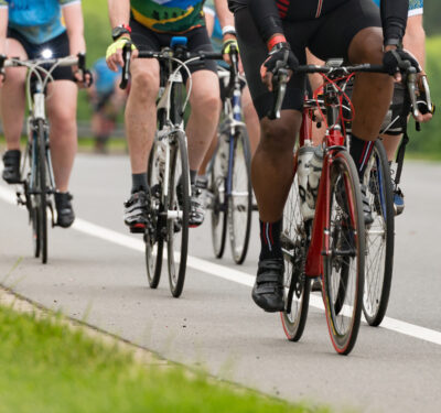 Group of cyclists competing in a race cropped square with a shallow depth of field and copy space